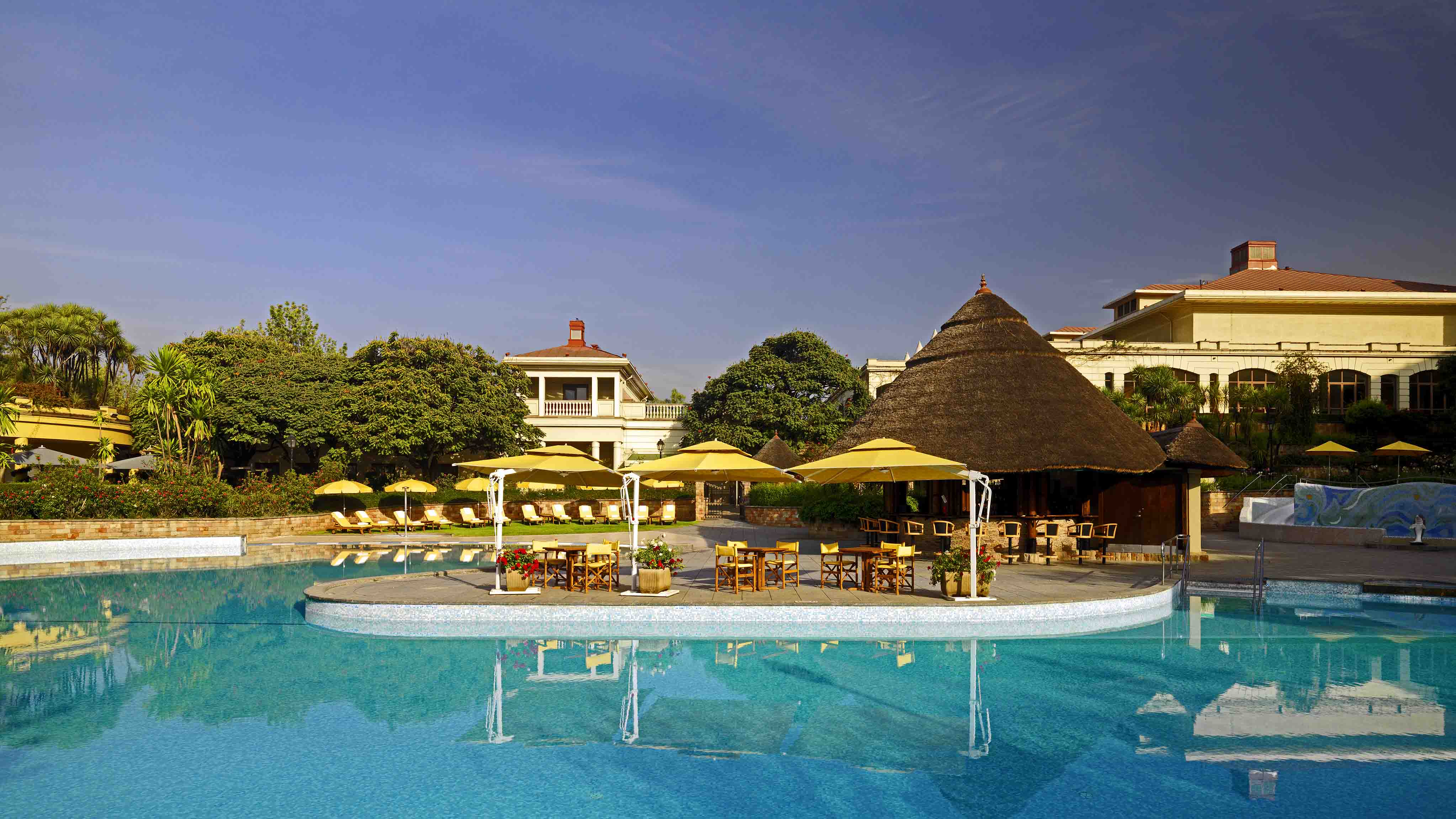 Sheraton Addis Swimming pool with thatched-roof restaurant and bar in background