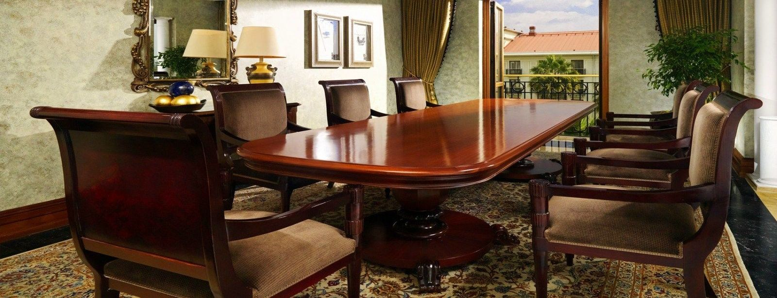 Executive Suite dining room with long wooden dining table and plush chairs